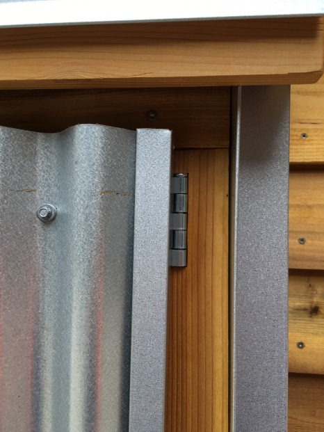 Layers of cedar and metal at small shed.