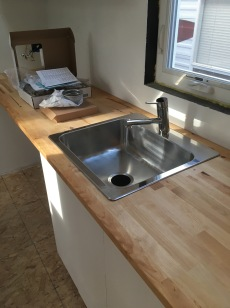Shiny stainless steel sink and faucet.